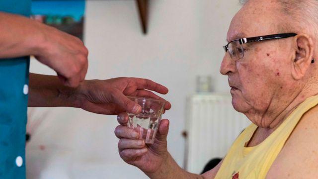 Un ayudante acerca un vaso de agua a un hombre mayor