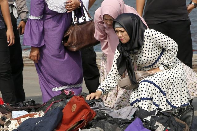 """Wife (R) of Lion Air flight JT-610 plane crash victim Indonesian policeman Mito looks for her husband""""s belongings at the collection point at Tanjung Priok Harbour, Jakarta, Indonesia, 31 October 2018."""