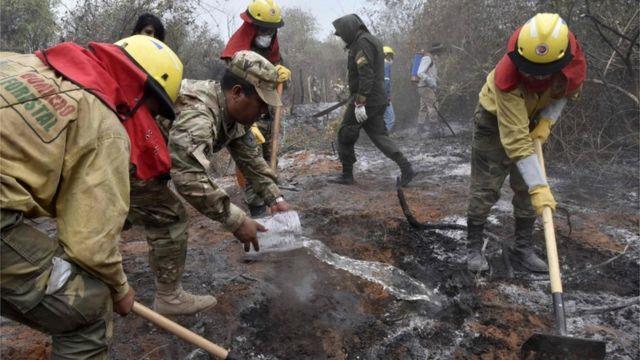 Trabajadores apagan incendios en Bolivia.