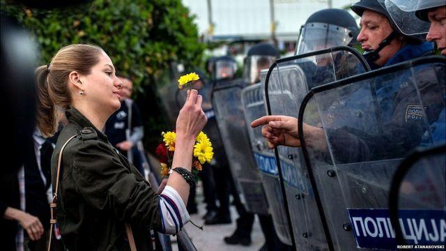 Una joven entrega una flor a un policía antimotines en protestas en Macedonia.