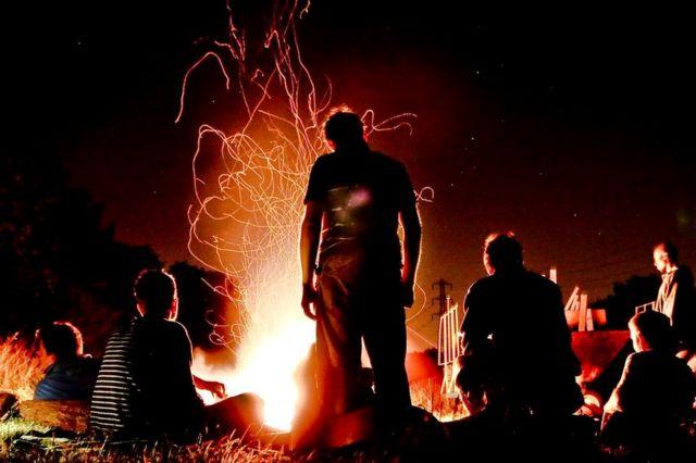 Pessoas reunidas em torno da fogueira de um acampamento