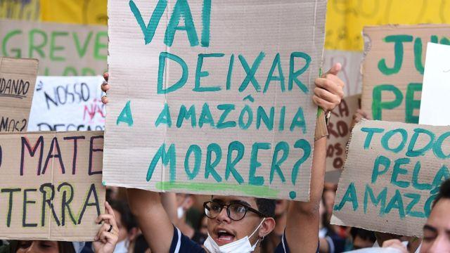 """Joven en Brasil con una pancarta que dice """"¿van a dejar morir a la Amazonia?"""""""