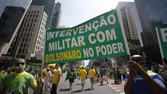 Homens seguram bandeira onde está escrito 'intervenção militar'