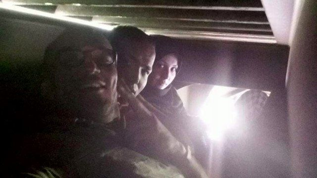 Migrants take a selfie travelling under a train