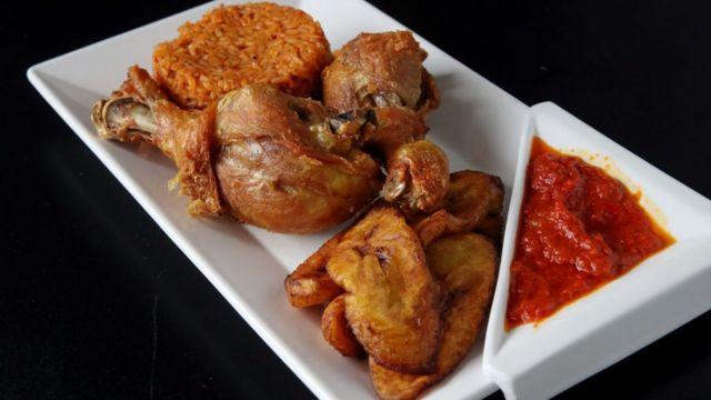 Riz jollof avec poulet et bananes plantains frites au restaurant nigérian Obosa dans le quartier de Roslindale à Boston.