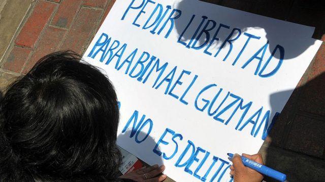 """Persona escribiendo en un cartel """"Pedir libertad para Abimael Guzmán no es delito""""."""