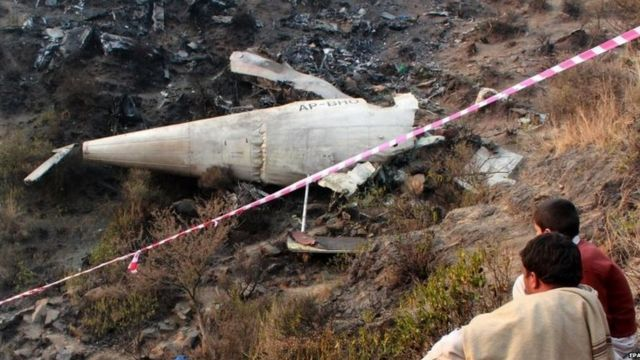 Local residents sit beside the wreckage of a Pakistan International Airlines turboprop passenger plane after it crashed near Havelian, Pakistan (08 December 2016)