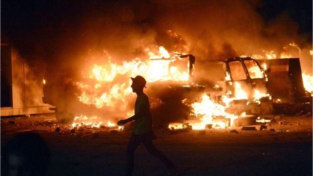 عراقي يمر أمام شاحنات عسكرية تلتهمها النيران في البصرة