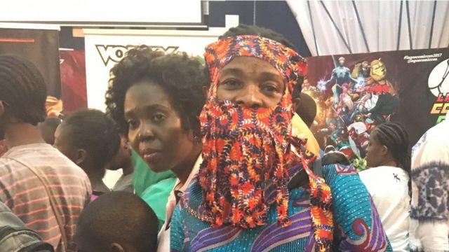 Woman wey put ankara for face.
