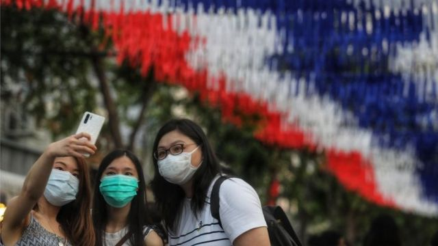 Women wearing protective facemasks pose for a selfie at the Chatuchak weekend market in Bangkok on February 8, 2020