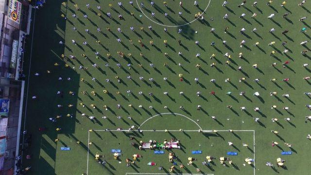 Vista aérea de campo de futebol em Paraisópolis, com dezenas de pessoas enfileiradas, mantendo o distanciamento social, durante formação de 'presidentes de rua' e brigadistas em Paraisópolis