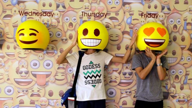 """Dos personas probándose unas """"máscaras"""" de emojis en China"""