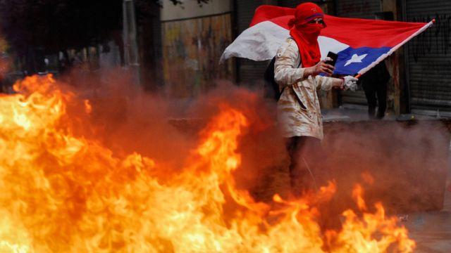 Homem com mão sangrando e bandeira do Chile em protesto