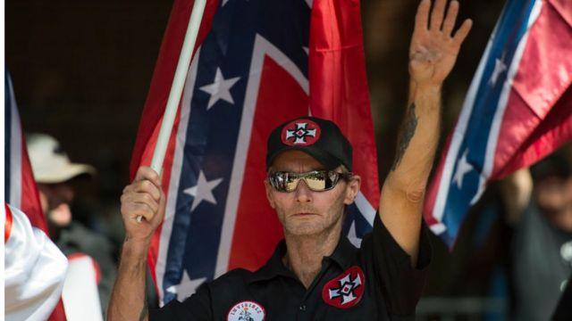 Un supremacista hace el saludo nazi con una bandera de la confederación y las cruces símbolo del Ku Klux Klan.