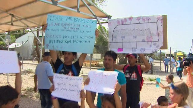 Migrants holding signs that ask for help