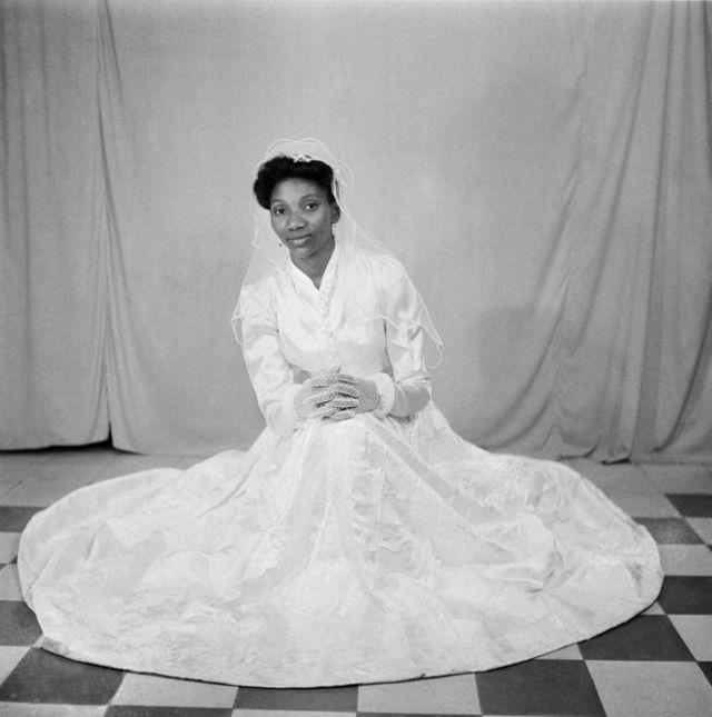 Une femme pose sur le sol du studio dans une robe de mariée blanche, des gants en dentelle et un voile.