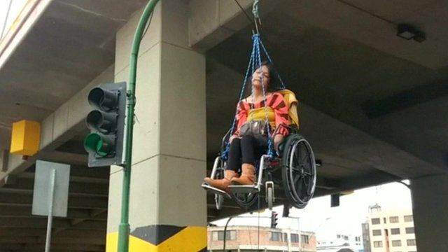 Woman in a wheelchair suspended from a bridge