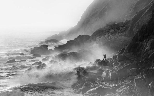 Fisherman on Rocks in Strong Westerly Winds Porth Nanven, Cornwall