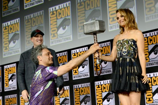 Natalie Portman holding a hammer which has just been handed to her.