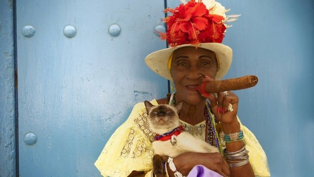 A woman with a cat in her arms and smoking a cigar in Cuba