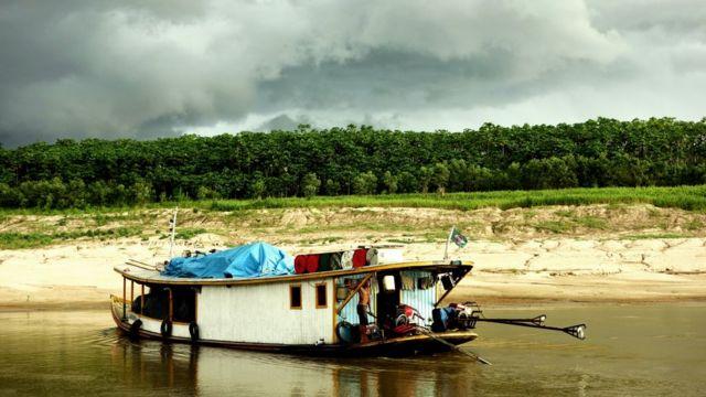 Um barco razo (conhecido como chalana ou canoa) na estação seca no Rio