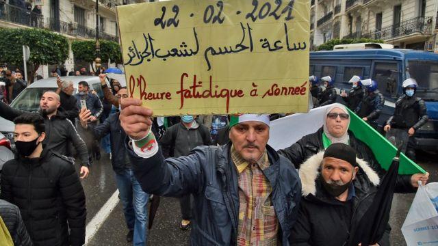 """متظاهرون يرفعون لافتة كتب عليها """"ساعة الحسم لشعب الجزائر"""""""
