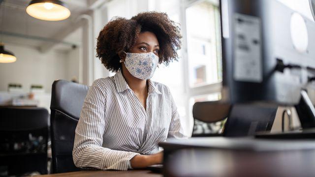 Una oficinista con máscara