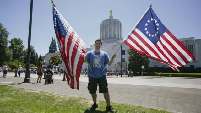 Un joven sostiene dos tipos de banderas de EE.UU.