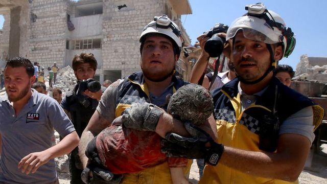 Membros da defesa síria, conhecidos como capacetes brancos, retiram uma criança ferida debaixo de escombros depois de um ataque russo na província de Idlib em julho de 2019