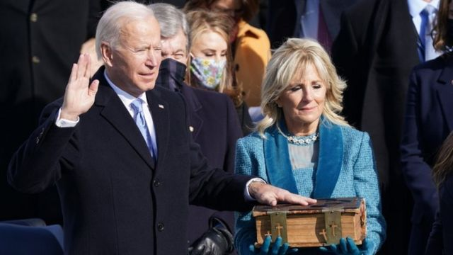 Joe Biden takes his oath with one had on the Bible