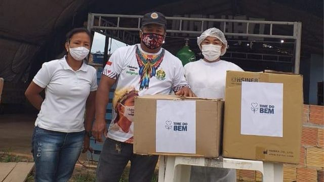 Vanda e dois homens de máscara olham para foto, em área externa, ao lado de mesca com duas caixas de papelão