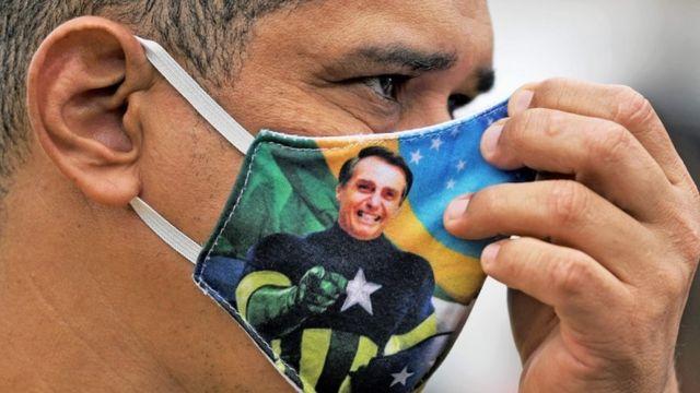 Homem de perfil com máscara estampada com imagem de Bolsonaro
