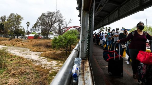 Migrants mostly form Central America wait in line to cross the border at the Gateway International Bridge into the US from Matamoros, Mexico to Brownsville, Texas, on March 15, 2021.