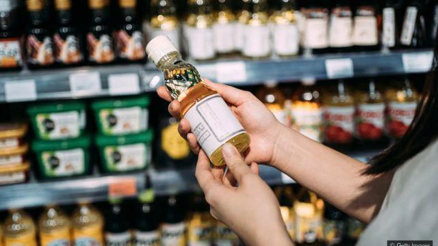 Une femme achète une bouteille d'huile dans un supermarché