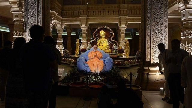 ગાંધીનગરના અક્ષરધામ મંદિરમાં ભગવાન સ્વામીનારાયણ મૂર્તિની પાસે રાખવામાં આવેલું પ્રમુખ સ્વામીનું જીવંત ચિત્ર