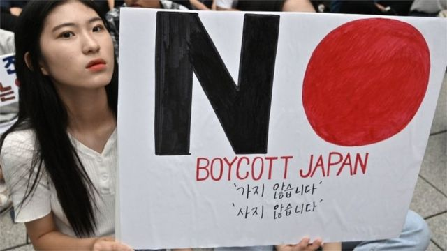 "South Korean protesters hold a sign saying ""Boycott Japan"" in Seoul"