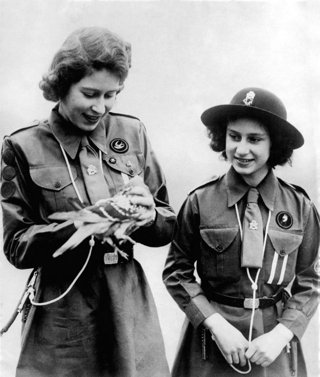Queen Elizabeth II, when she was still a princess, showing her sister Margaret one of the carrier pigeons.