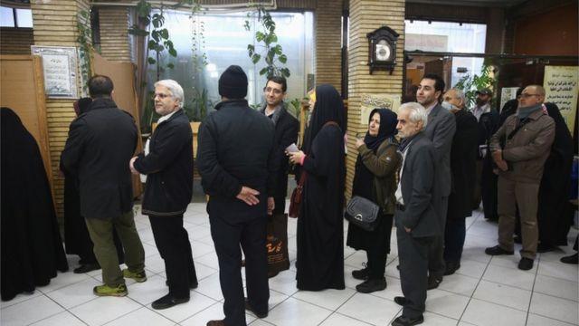 عدد من الناخبين والناخبات يصطفون انتظارا لفتح باب أحد مراكز التصويت في العاصمة طهران