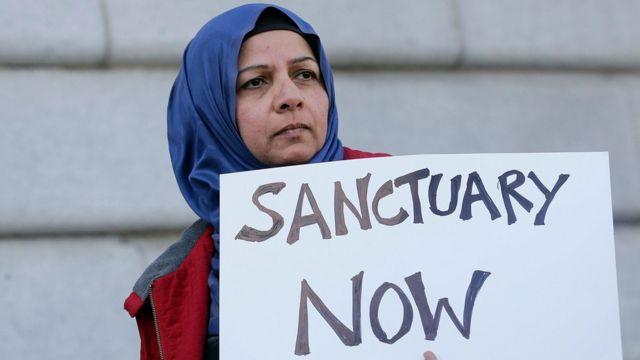 """Una mujer musulmana sostiene un cartel que dice """"Santuarios ahora""""."""