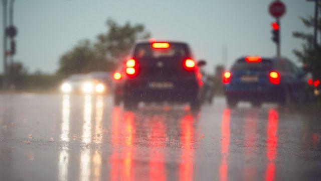 Autos vistos desde atrás, con las luces de frenos encendidas, en un día lluvioso