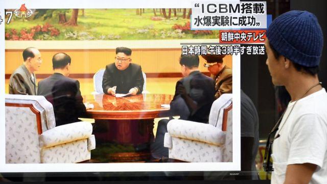 日本東京街頭一名路人探頭觀看路旁電視機播放的朝鮮核試驗新聞報道(3/9/2017)