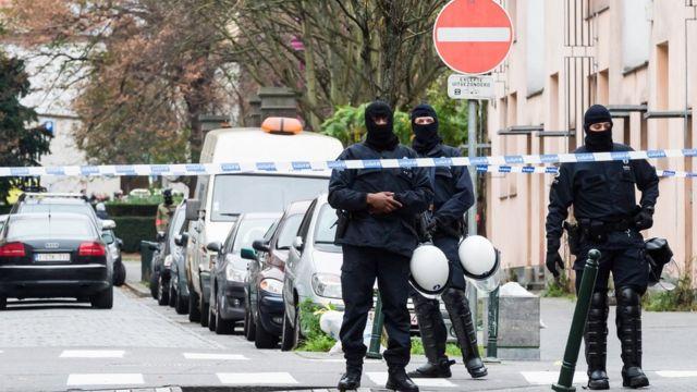 Armed police guard a street in Molenbeek, Brussels on Monday, Nov. 16, 2015