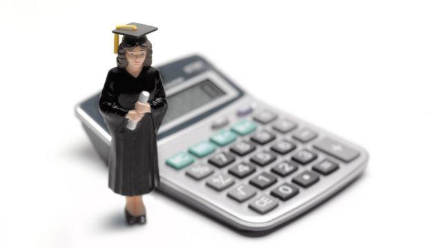 Una muñeca vestida de graduada y una calculadora