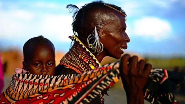 A woman from the Turkana tribe carries a baby on her back at the Lake Turkana Festival in Loiyangalani, near Lake Turkarna in Northern Kenya on May 19, 2012