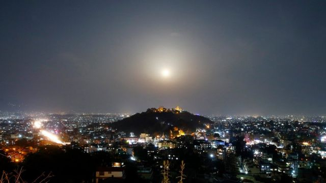 A full moon rises behind the Swayambhunath Stupa in Kathmandu, Nepal, 31 March 2018.