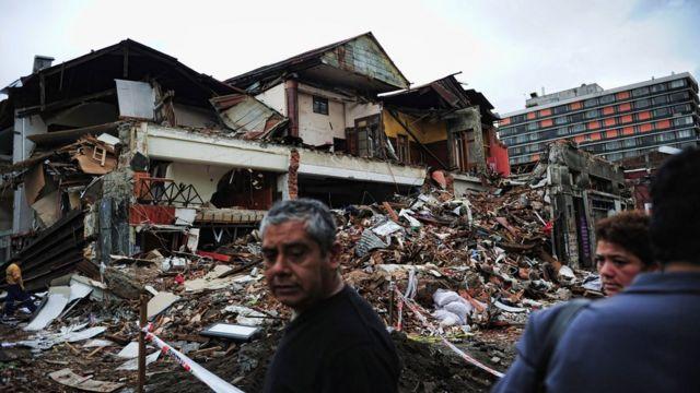 Personas observan edificios en escombros en Concepción, afectada por el terremoto de Chile de 2010.