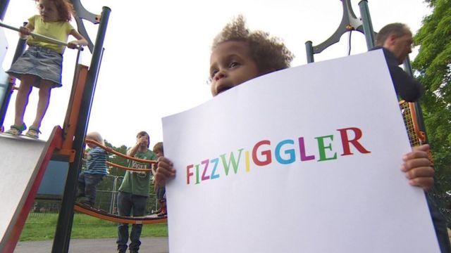 Child holding up Fizzwiggler sign