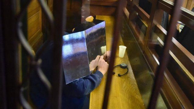 المتهم يخفي وجهه وهو ينتظر بدء محاكمته في محكمة أمنية خاصة في برلين يوم الاربعاء