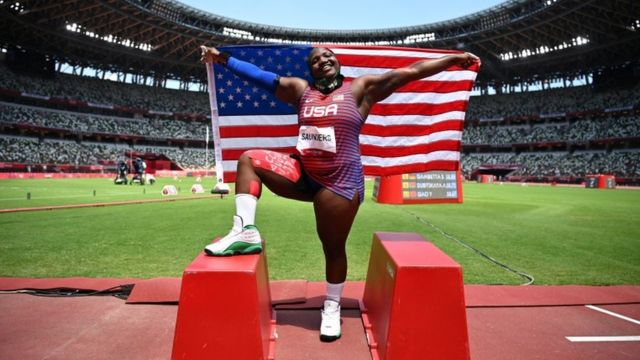 Raven Saunders poses with her national flag as she celebrates winning the silver medal