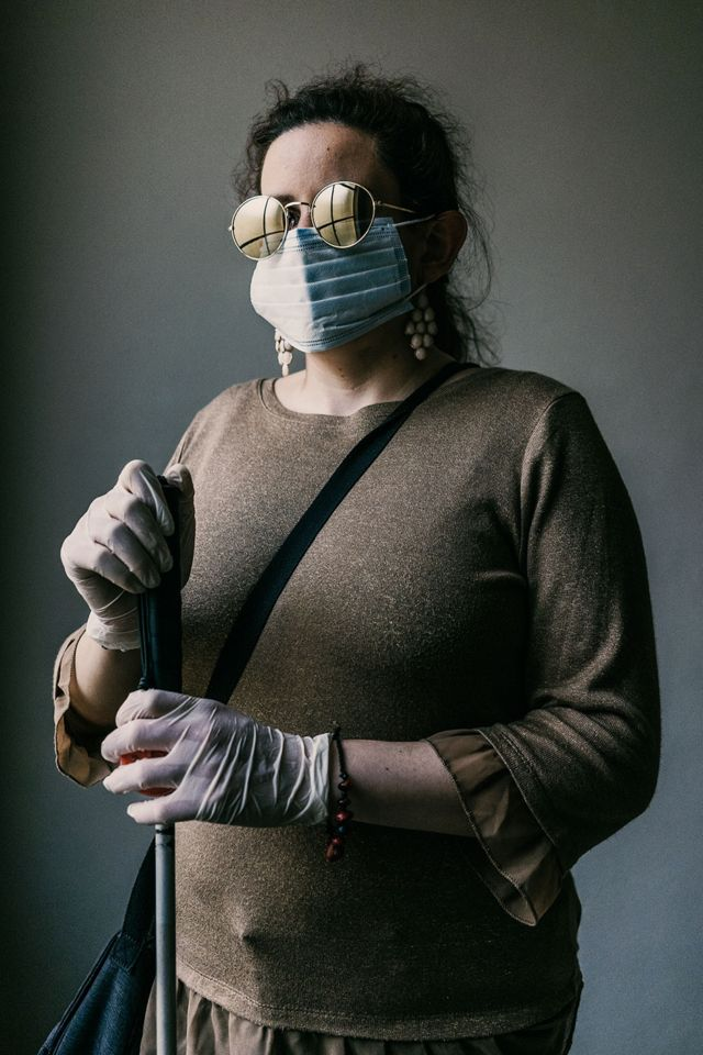 A blind woman stands with her walking cane whilst wearing a face mask and gloves